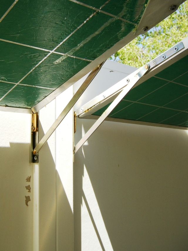 Whitco window stays that form hinges to support sun mirror panels in winter are set here to make the same panels give summer shade.